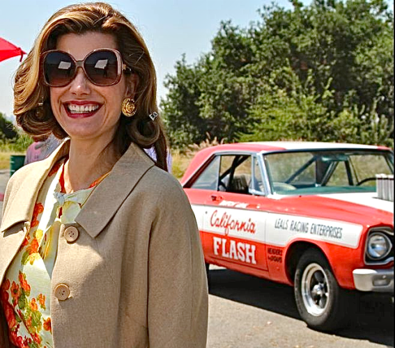 On location during Snake & Mongoose movie shoot: lovely Gilligan Gibbons, in the role of Brenda Greer and Butch Leal's California Flash, a '64 Plymouth A/FX drag car, share craft services.